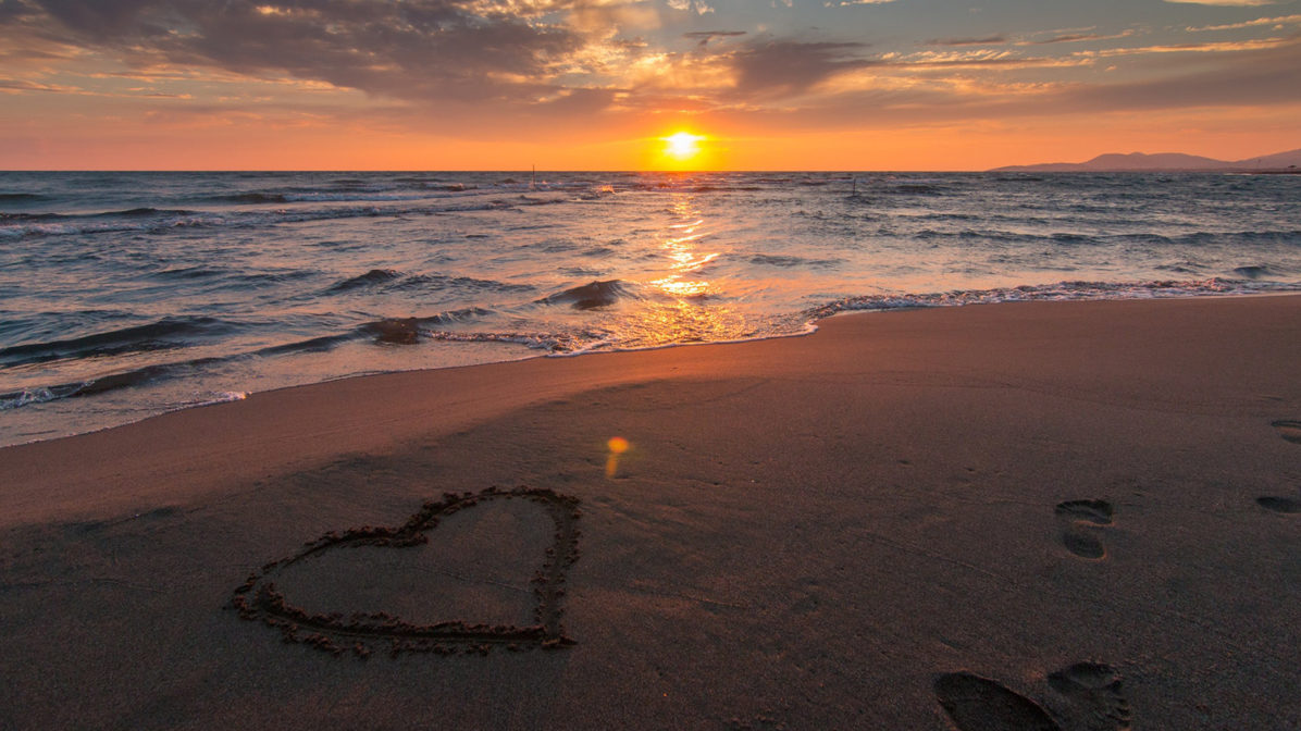 Sunset on a beach with heart drawn in the sand