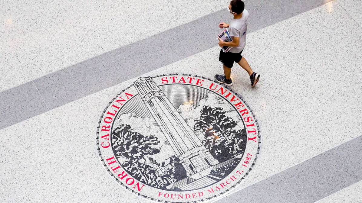 A student walks over the seal on the floor of Talley Student Union