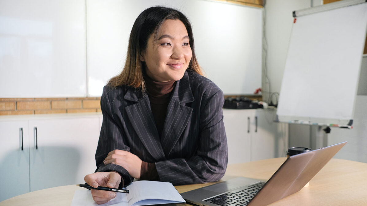 Smiling Asian woman in an office with computer
