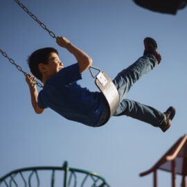 a young child enjoys swinging on the swing set of a playground